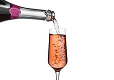 Pouring pink rose champagne from bottle to glass Stock Images