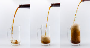 Pouring process of dark stout beer into a beer glass mug, splashes, drops and froth around glass Stock Photography