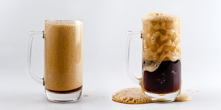 Pouring process of dark stout beer into a beer glass mug, splashes, drops and froth around glass Royalty Free Stock Image