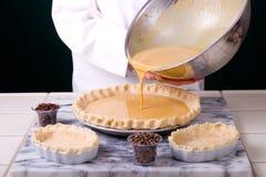 Pouring Pumpkin Batter. Close up capture of a Pastry Chef pouring pumpkin batter into formed pie crust Stock Photo