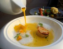 Pouring pumpkin soup into seared scallops. Pouring soup, Closeup of pumpkin soup into seared scallops and parmesan foam in white plate with blur boken food dish Stock Image