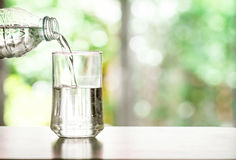 pouring purified fresh drink water from the bottle on table in Royalty Free Stock Photography