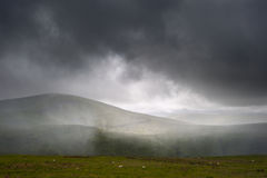 Pouring rain in mountain landscape. Beautiful landscape across countryside to mountains in distance with moody sky Stock Image
