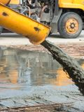 Pouring ready-mixed concrete after placing steel reinforcement to make the road by mixing mobile the concrete mixer Royalty Free Stock Photo
