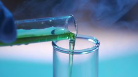 Pouring reagent into test tube. Concept - medical research, drug testing, genetic experiments stock footage