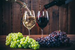 Pouring Red And White Wine Into The Wine Glasses With A Bunch Of Red And White Grapes Against Stock Image