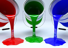 Pouring red, green and blue paint. Three paint tins pouring red, green and blue colours onto a white to grey background. The three colours represent the RGB Stock Images