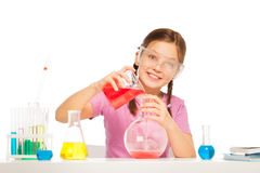 Pouring red liquid reactant from volumetric glass Royalty Free Stock Photo