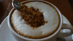 Pouring red sugar in to hot coffee. In white cup on wood table in coffee shop stock footage