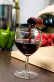 Pouring red wine. In kitchen Stock Photo