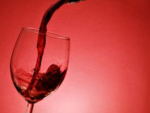 Pouring red wine. Pouring wine over red background stock photo