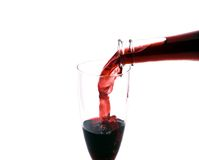 Pouring red wine. Red wine pouring in the glass from the bottle on white background Stock Images