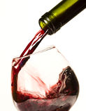 Pouring red wine. Close up on bottle and pouring red wine Royalty Free Stock Photo