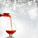 Pouring red wine against holiday lights Royalty Free Stock Photos