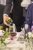 Pouring red wine from bottle into glass at the Party table decorated with beautiful flowers stock photography