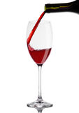 Pouring red wine from bottle to glass on white Stock Photography