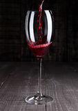Pouring red wine from bottle to the glass on wood Stock Photo