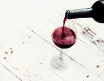 Pouring red  wine from bottle in wine glass on vintage white wo. Oden table  with copyspace Royalty Free Stock Photos