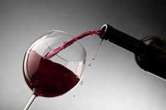 Pouring red wine from bottle into the wineglass Stock Image