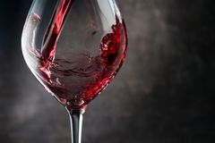 Pouring red wine. Dark background royalty free stock image