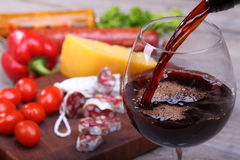 Pouring red wine and food bachground. Pouring red wine into glass and food background Stock Photos