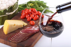 Pouring red wine and food bachground. Pouring red wine, cheese, bacon and tomato Royalty Free Stock Photos