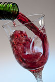 Pouring red wine into a glass Stock Images