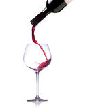 Pouring red wine into glass. Over white background Royalty Free Stock Photo
