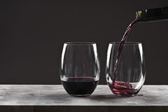 Pouring Red Wine into Glass. Against Brown Background royalty free stock images