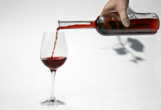 Pouring red wine in glass. Red wine from bottle is pouring into a glass of red wine. Vine leaf as shadow in background Stock Image