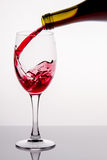 Pouring red wine into a glass Stock Photos