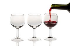 Pouring red wine into glass. On white background Royalty Free Stock Photography