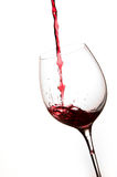 Pouring Red Wine in a Glass. With White background Stock Images