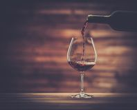 Pouring red wine into the glass Stock Photos