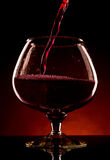 Pouring red wine into glass. Pouring red wine into a big glass with splashing on dark orange background Royalty Free Stock Photo