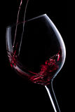 Pouring red wine in glass. Red wine pouring into a wine glass  on black background Royalty Free Stock Photography