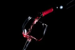 Pouring red wine glass black background Royalty Free Stock Photography