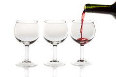 Pouring red wine into glass from bottle. On white background Stock Photography