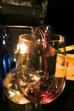 Pouring red wine into glass from a bottle. In candlelight Stock Images