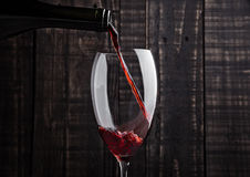 Pouring red wine into the glass from bottle Stock Photography