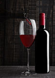 Pouring red wine into the glass from bottle Royalty Free Stock Photography