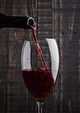 Pouring red wine into the glass from bottle Stock Photos