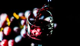 Pouring red wine in a glass, celebration of a moment with a glas. S of wine, exquisite liquor for gourmets, winery Stock Photography
