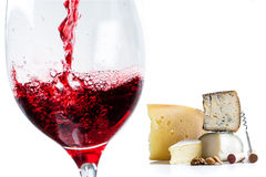 Pouring red wine in glass with cheese in background. Stock Photo