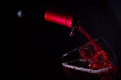 Pouring red wine glass on dark light Royalty Free Stock Images