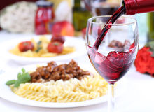 Pouring red wine into a glass. Pouring red wine and food background Stock Images