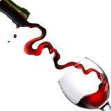 Pouring red wine in glass goblet isolated on white Royalty Free Stock Photos
