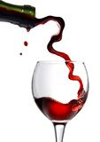 Pouring red wine in glass goblet isolated on white Royalty Free Stock Images