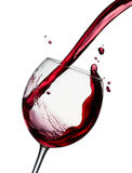 Pouring red wine. Pouring a glass of red wine isolated on white royalty free stock image