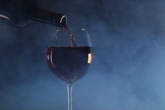 Pouring red wine into a glass. Pour red wine into a glass in the blue smoke Stock Image